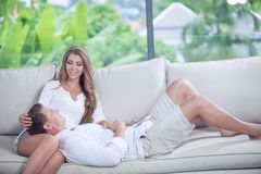 View of nice young couple is sitting on sofa in summer house Royalty Free Stock Photography