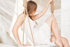 View of nice young lady swinging  in studio Royalty Free Stock Photography