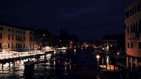 View of the night city on the river. Boats float on the water. stock footage