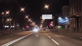 View of night city and road. Camera inside driving car. Crossroad stock footage