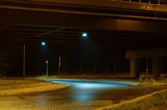 View of a night city street under a bridge in colorful lights stock photography