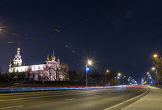 View of the night city with tram tracks and church Royalty Free Stock Image