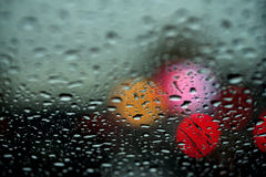 View of the night city through the window on a rainy night, raindrops fall on the windshield of the car. Concept life of Stock Photo