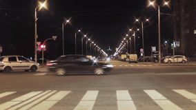 View of night crossroad with traffic lights and cars in city stock footage