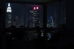 View of night skyscrapers of New York City Manhattan through windows of apartment. Top view of night midtown of Manhattan. royalty free stock photos