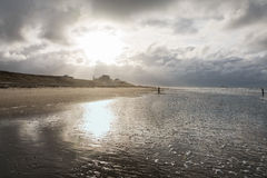 View of the North Sea. Rays of sunshine breaks through the storm clouds and illuminated promenade Stock Photography