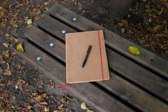 View on a notebook and pen on a wooden bench in the nature of meppen emsland germany royalty free stock images