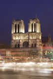 View of the Notre Dame Cathedral at evening with moving cars in Paris Stock Photos
