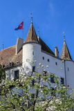 View at Nyon castle with flag waving on the roof through blooming tree. Switzerland royalty free stock photo