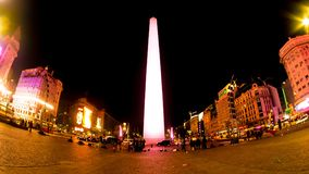 View on the Obelisk Monument in Buenos Aires in Argentina. BUENOS AIRES, ARGENTINA - AUGUST 12: View on the famous Obelisk Monument as traffic and People pass by royalty free stock image