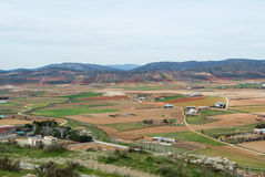 A view from observation deck to fields, farms and mountains near Consuegra town at spring cloudy day, Castilla La Mancha Stock Image