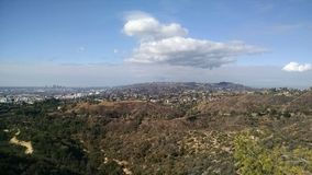 Mountaintop View of Los Angeles California with forest and light cloud cover royalty free stock photo