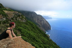 View at the ocean. Girl takes a view to the atlantic ocean at the north coast of Madeira, Portugal Stock Photo