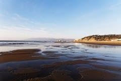 View of Ocean beach in San Francisco. Gentle surf lapping against a golden shore near Golden Gate Bridge in San Francisco Stock Photos