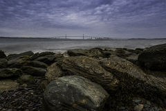 View of Ocean Bridge from Rocky Shore. Under dramatic cloudy sky. Newport Pell Bridge taken in Newport, Rhode Island Royalty Free Stock Image