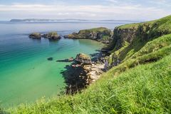 View of the ocean and Carrick-a-Rede island on the coast of County Antrim, Northern Ireland. Showing the emerald blue sea, the cliffs and the dark kelp beds stock images