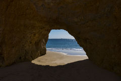 View of the Ocean from a cave in the scenic beach Praia dos Tres Irmaos in Alvor, Algarve, Portugal Stock Photo
