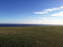 View of the Ocean on a Grassy Field Royalty Free Stock Photo