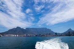 View from ocean on the harbor of Cape Town and the iconic Table mountain and Lions Head royalty free stock photography