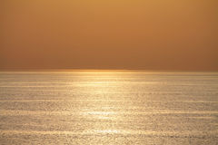 View on ocean in orange sunset with texture reflection in water Royalty Free Stock Photo