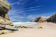 View of the ocean between rocks of Praia de Augas Santas. A fragment of the beach of cathedrals in summer day in good weather. The blue sky with numerous royalty free stock photography