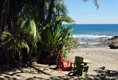 A view of the Ocean and Rocky Coastline with Green and Red Adirondack Chairs royalty free stock photos