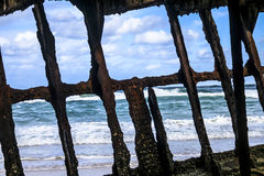 View of ocean through shipwreck. Ocean through rusty hull of shipwreck with barnacles. Fraser Island, Australia Stock Photography