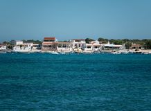 View from ocean to shore of Algarve, Portugal with boats and beach houses on horizon. royalty free stock photos