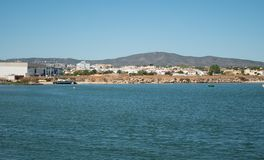 View from ocean to shore in Algarve, Portugal in summer with boat on beach, houses and hills in background. Bright sunny day in summer stock photos