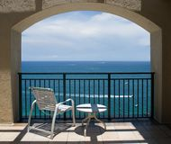 View of Ocean Under Arch. An inviting view of the ocean through an arch of a balcony Stock Images