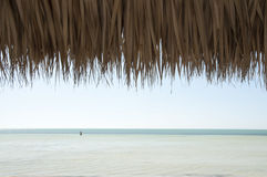 View of the ocean under tiki hut roof royalty free stock photography