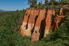 View of ocher land cliffs under a sunny blue sky, in a park near Roussillon. Stock Photography