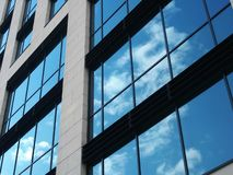 Free View Of A Modern Commercial Building With Large Mirrored Windows Reflecting Blue Sky And White Clouds Stock Photo - 155529950