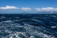 Free View Of Atlantic Ocean And Distant Mountains, Choppy Water, Calm Blue Sky With White Clouds Royalty Free Stock Image - 143464516