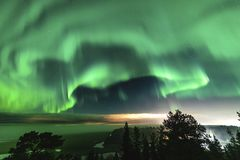 Free View Of Brilliant Green Aurora Shining Over Swedish Foggy Forest Landscape In Mountains, Light Rays From A Village And Northern Stock Image - 162576591
