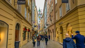 View Of Famous Medieval Street Of Salzburg, Austria. Currently A Lively Shopping Area. Wolfgang Amadeus Mozart Was Born. Clock Tow Stock Image