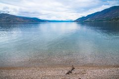 Free View Of Pebble Beach, Calm Lake, Mountains, And Overcast Sky At Antler`s Beach, Peachland, British Columbia, Canada Royalty Free Stock Images - 164000269