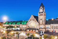 Free View Of The Illuminated Old Railway Station Building With Clock Tower In Metz City Stock Photos - 172443423
