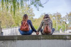 Free View Of Two Girlfriends Girls Sitting On A Wall And Looking At The Landscape Hand In Hand And Lovingly Royalty Free Stock Photography - 162569047
