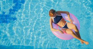 View Of Young Brunette Woman Swimming On The Inflatable Pink Ring Royalty Free Stock Photography