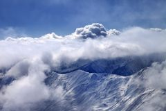 View on off-piste slope at mist and sunlight clouds Royalty Free Stock Image