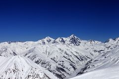View on off-piste slope, winter snowy mountains and blue clear s Stock Photography