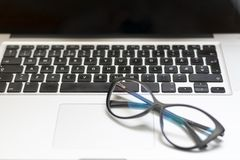 Desk with laptop, glasses and other items stock photography