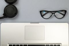 Desk with laptop, glasses and other items royalty free stock photo