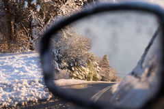 View through offside car mirror. View through driver's offside mirror showing double white continuous road markings and snow covered for trees Stock Photos