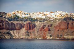 View of Oia village with white houses on red rocks caldera of Santorini Island, Greece. View of Oia village with white houses on red rocks caldera of Santorini royalty free stock photography
