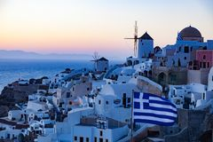View of Oia Village with windmills at sunset, Santorini, Greece stock photos