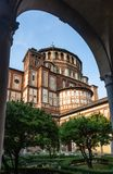View of the old basilica through the arch of the portico in Milan, Italy royalty free stock photography