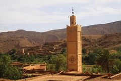 View on old berber arabian village with clay brick houses in valley with greenery and minaret stock images