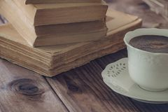 Old books along with a cup of coffe. stock photo